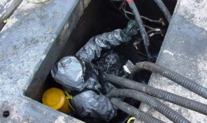 Spill responder performs confined space entry to decontaminate cement utility vault.
