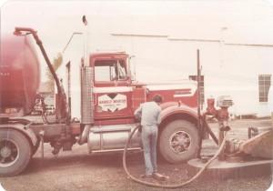 Employee, John Barnes, refueling tractor. (October 1980)
